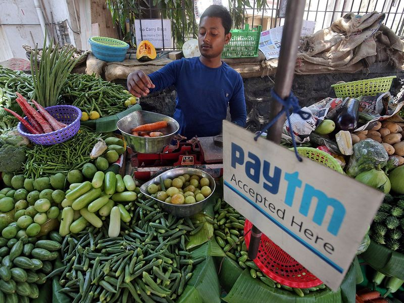 A vendor weighs vegetable next to an advertisement of Paytm