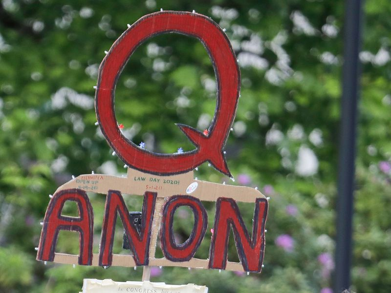 File photo: A person carries a sign supporting QAnon at a protest rally in Olympia