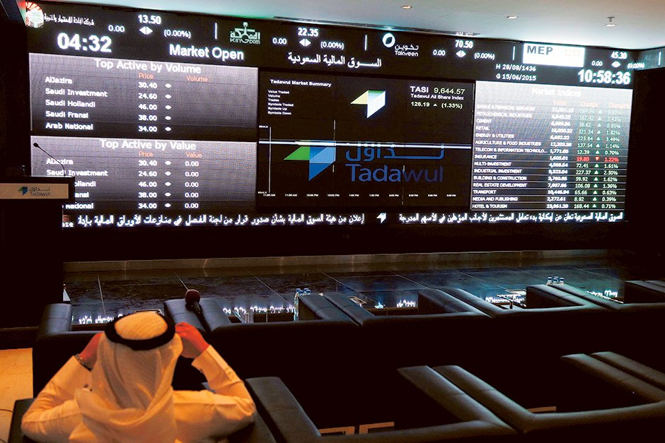 A trader monitors screens displaying stock information at the Saudi Stock Exchange in Riyadh  yesterday. The chief executive of Saudi Arabia's stock exchange said yesterday he expected a flurry of licenses allowing the first foreign investors to buy shares there in coming weeks.