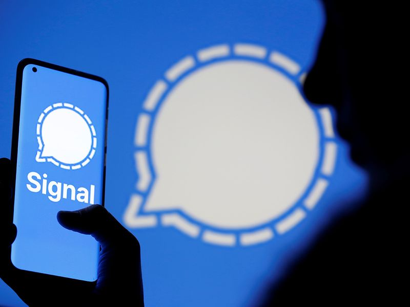 A woman holds a smartphone displaying the Signal messaging app logo.