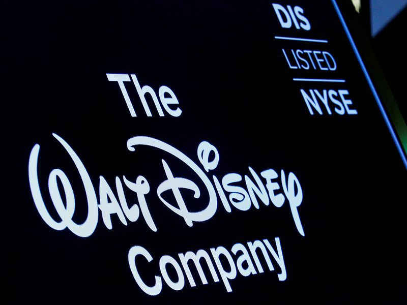 A screen shows the logo and a ticker symbol for the Walt Disney Company on the floor of the New York Stock Exchange.