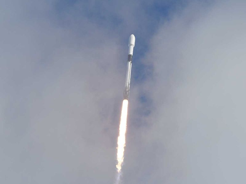 A SpaceX Falcon 9 peeks through the clouds after it lifts off on Pad 40 at Cape Canaveral Space Force Station.