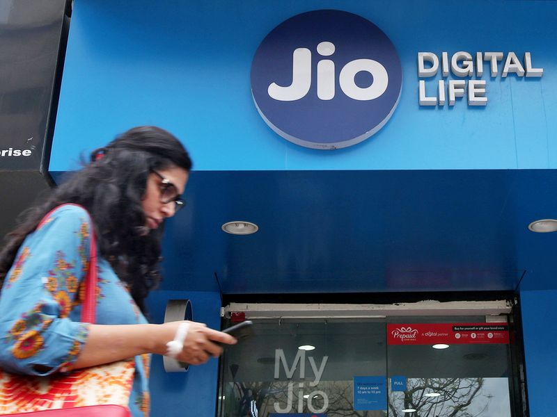 File photo: A woman checks her mobile phone as she walks past a mobile store of Reliance Industries' Jio telecoms unit