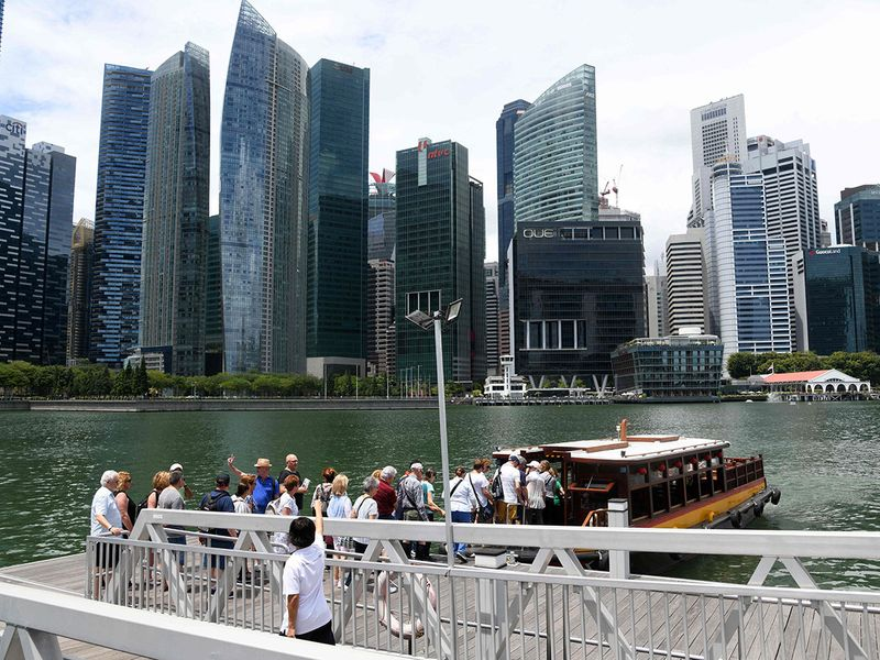 Visitors boarding a boat for a tour along the Singapore river in Singapore