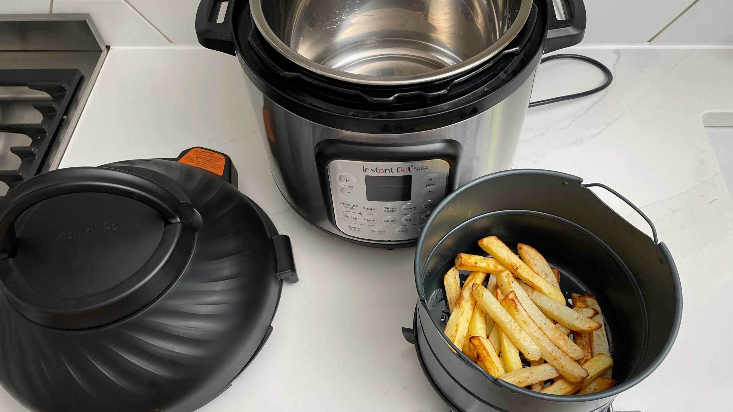 Instant Pot Duo Crisp & Air Fryer next to some fries that were cooked in it