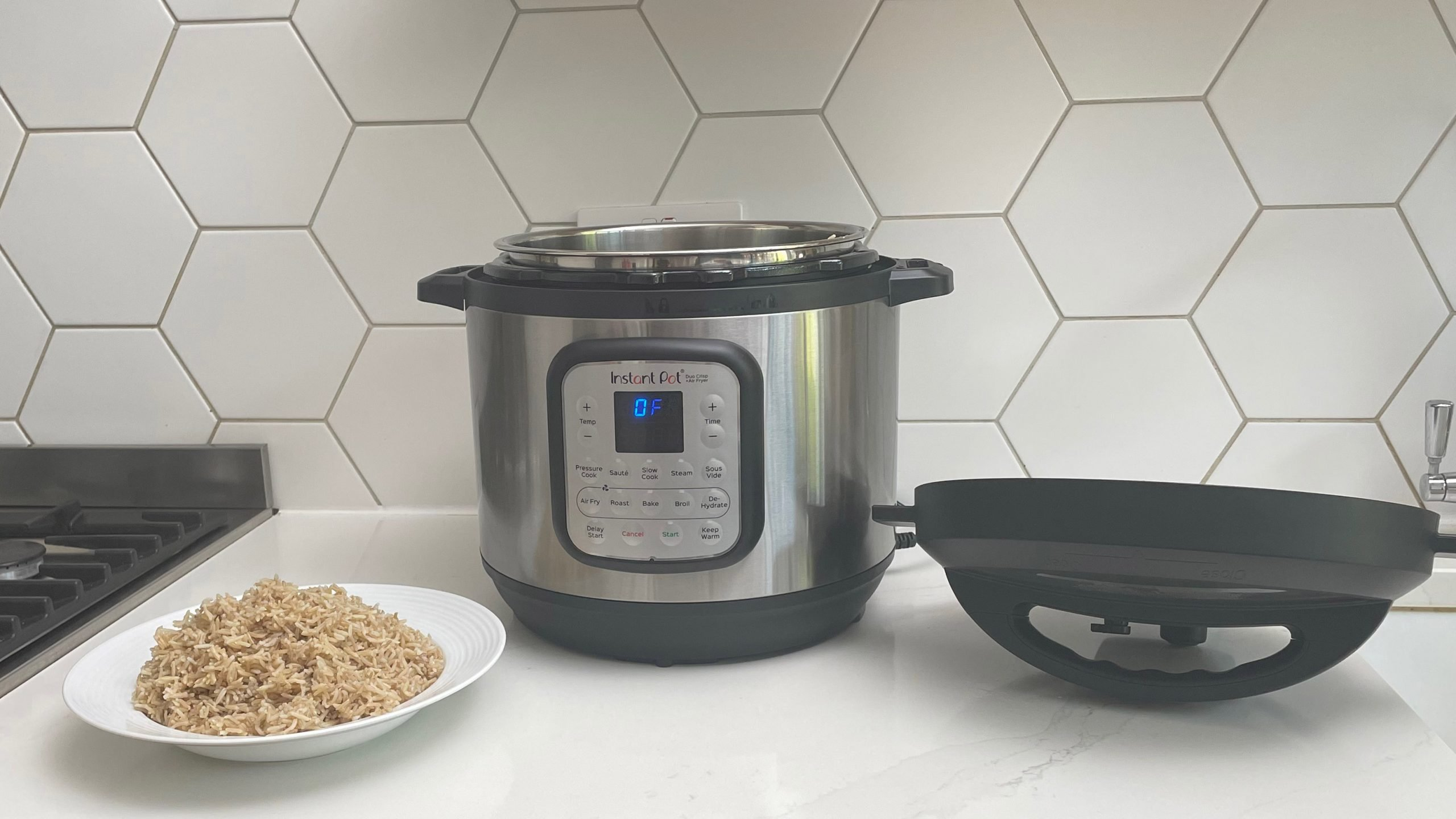 Instant Pot Duo Crisp & Air Fryer on a kitch countertop next to a bowl of rice